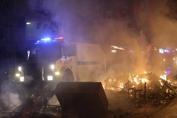 An armoured police vehicle drives through a barricade on fire during a demonstration in Istanbul